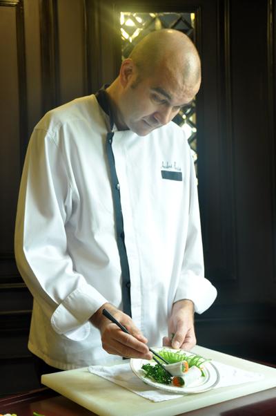 Ông Andre Bosia, bếp trưởng nhà hàng 1915 Indochine cẩn thận trang trí từng món ăn trong bữa tiệc. Ông Bosia đang trang trí cho món khai vị Gỏi củ sen hải sản. Từng miếng củ sen trắng giòn dân dã được thái lát khéo léo.