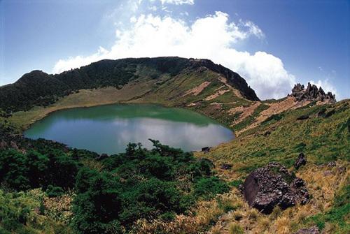 núi đá có cây xanh, hồ nước hình tròn giữa lòng núi