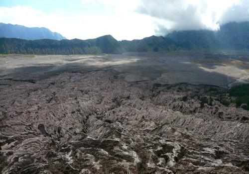 Sau khi đã thỏa sức ngắm nhìn cảnh bình minh rực rỡ, bạn phải thuê một chiếc xe jeep để đi đến ngọn núi lửa nổ tiếng Bromo. Dưới chân núi là cả một vùng đất rộng mênh mông, bao phủ bởi một màu xám tro cùng những cát và đá.