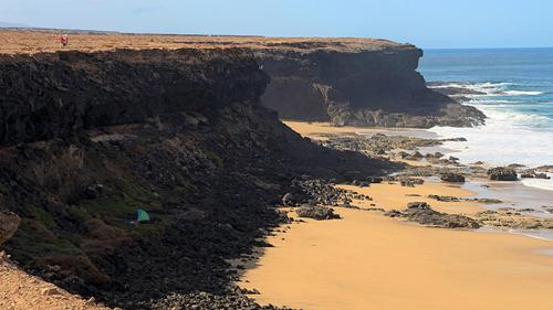 Aljibe de la Cueva, Fuerteventura, đảo Canary, Tây Ban Nha Được xem là một viên ngọc của Fuerteventura, bãi biển Aljibe de la Cueva nằm nép mình dưới chân vách đá màu vàng nâu đầy ngoạn mục. Nơi đây đặc trưng với sóng to, gió lớn và những bãi đá nham thạch. Đứng trên những bãi đá vàng và chìm đắm trong cảnh sắc tuyệt đẹp, cẩm nhận những cơn gió biển, vị mặn của muối và lắng nghe nhữn giai điệu được cất lên từ sóng vỗ, đơn giản chỉ là đển tận hưởng hương vị của thiên nhiên.