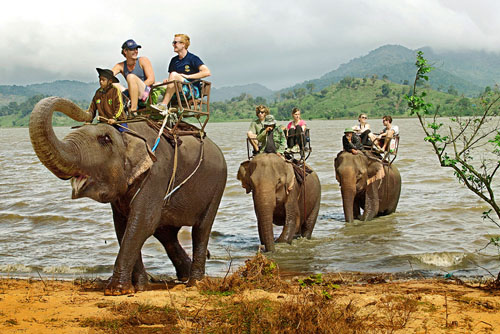 Du khách thích thú khi cưỡi voi vượt sông. Ảnh: vietnamtourism