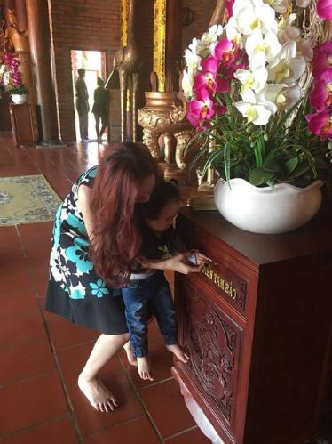 Noah được mẹ Diễm Hương hướng dẫn bỏ tiền vào hòm công đức. Ảnh: FBNV.
