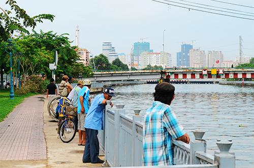 Nhiều người dân hiếu kỳ vẫn ra khu vực ven kênh để quan sát. Ảnh: Phong Vinh