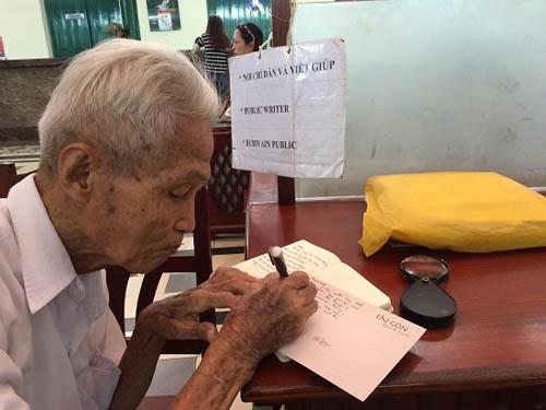 Ông Dương Văn Ngộ cẩn trọng dùng kính lúp đọc từng câu chữ của khách rồi dịch và viết thư. Ảnh: Mỹ Phượng