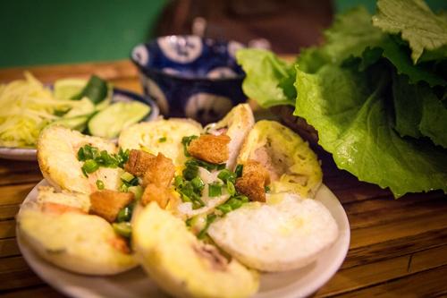 Bánh căn nhân thập cẩm ăn kèm rau sống.