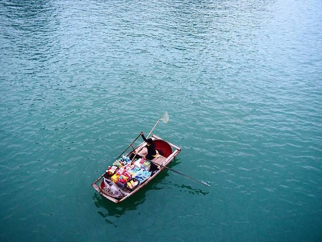 Khi dạo chơi ở vịnh Hạ Long, du khách sẽ rất dễ thấy những người dân địa phương bán hàng hóa lặt vặt trên chính các thuyền tre mộc mạc của họ. Ảnh: wanderlustrials.