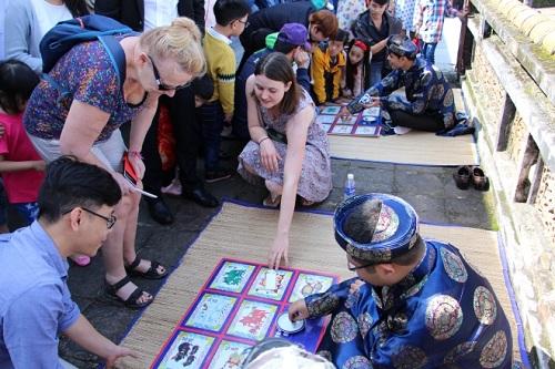 Khách nước ngoài thích thú với trò bài vụ, một trò chơi phổ biến ở Huế dịp Tết. Ảnh: Võ Thạnh.