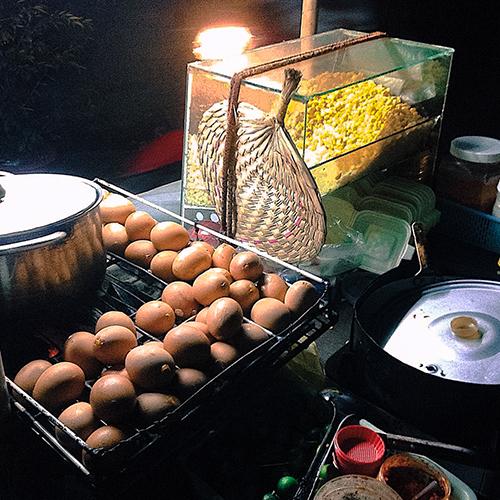 Trứng gà nướngMột trứng gà nướng có giá 10.000 đồng. Có lẽ vì giá khá hời này mà đây là món ăn được nhiều bạn trẻ ưa thích. Trứng được đánh tan bên trong cùng các loại gia vị rồi đem nướng trên than đỏ cho tới khi chín. Khi có khách gọi, người bán sẽ nướng sơ lại cho nóng rồi mang ra.Trứng khi ăn có độ giòn sật, chấm với muối tiêu chanh và ăn kèm với rau dâm. Trứng gà ăn ngon nhưng nhanh no. Ở phố Tây, món ăn này thường bán kèm trên những xe bắp xào. Ảnh: Mary.