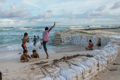 Trẻ em chơi đùa trước bờ kè thô sơ bằng bao cát chắn biển.Ảnh: NG.