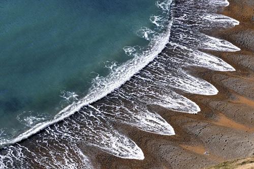 Những con sóng có hình cánh hoa (hay hình lười dao găm) ở bãi biển Jurassic, Dorset, Anh. Ảnh: AmusingPlanet.