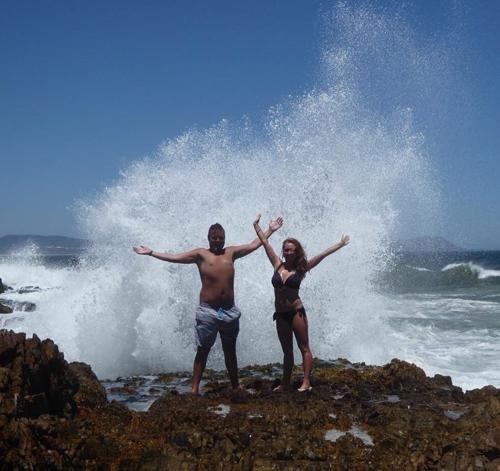 Hai vợ chồng mải chụp ảnh và không để ý đến những cơn sóng lớn phía sau. Ảnh: Sun.