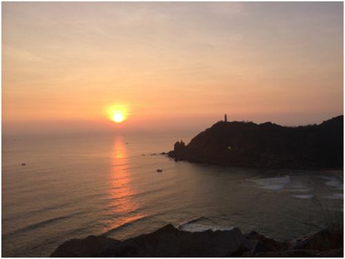 Ánh nắng mặt trời đầu tiên của Việt Nam mang một vẻ đẹp hoang sơ, cạnh đó là ngọn hải đăng Đại Lãnh lâu đời.