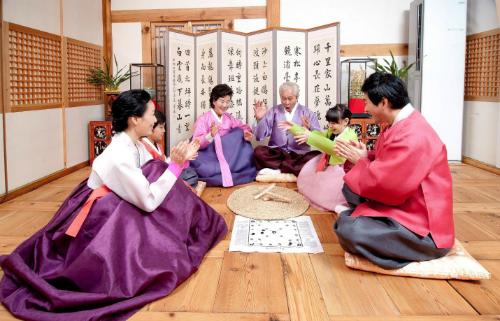 Các thành viên gia đìnhcùng nhau chơi trò yutnori. Ảnh: k14.