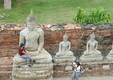 Hình ảnh người phụ nữ ngồi lên lòng tượng Phật khiến người dân Thái Lan không hài lòng. Ảnh: AO.
