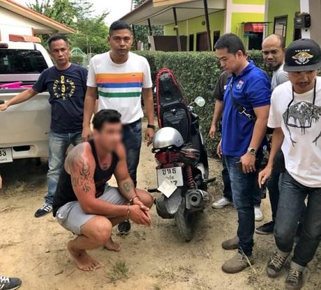 Nahum ngồi bên chiếc xe máy che biển khi bị cảnh sát bắt. Ảnh:Phuket Gazette.