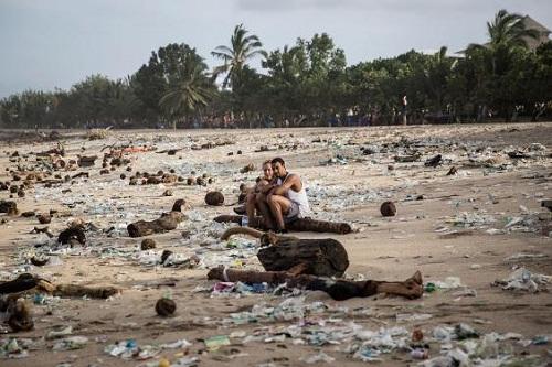 Du khách ngồi giữa bãi biển ngập rác. Ảnh:Independent.