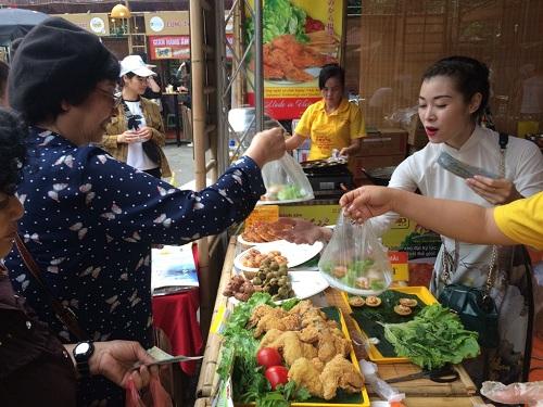 Khách tham quan thích thú với món bánh khọt tại gian hàng ẩm thực miền Tây. Ảnh:Phạm Huyền.