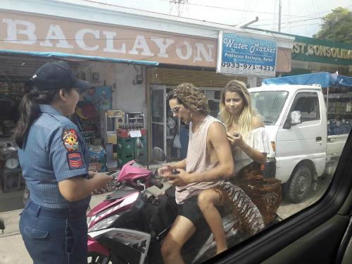 Cảnh sát ghi vé phạt cho cặp du khách, tặng thêm một chiếc sarong để cô che chắn khi ngồi xe. Ảnh:Facebook.