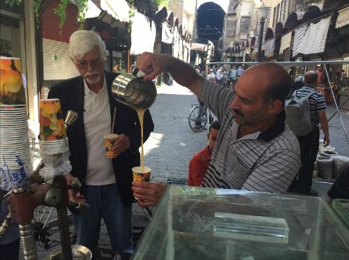 Thomas mua nước cam tươi từ một xe rong trong chợ Damascus. Ảnh:CNN.