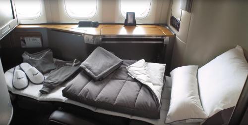 Bộ ga gối, chăn, quần áo ngủ cùng dép đi trong nhà củakhoang hạng nhất. Ảnh:American Airlines.