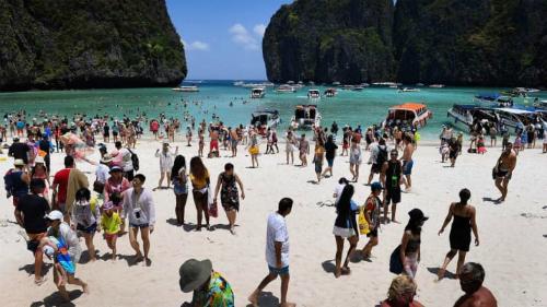 Hàng loạt du khách xếp hàng trên bãi cát để đợi lượt lên thuyền cao tốc vào buổi sáng. Ảnh: AFP.