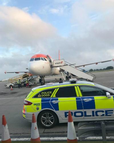 Xe cảnh sát đậu trước vị trí của máy bay hãng EasyJet sau khi một nhóm khách gây rối trên máy bay. Ảnh: Sun.