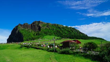 Đảo JejuĐảo Jeju được mệnh danh là hòn đảo hòa bình và được công nhận là một trong 7 kỳ quan thiên nhiên của thế giới.Vào mùa hè, Jeju như khoác lên mình chiếc áo xanh biếc của cây cối, núi đồi, chấm phá bằng những gam màu trầm mặc của đá.Đến với hòn đảo này, chắc chắn du khách không thể bỏ qua đỉnh núi mặt trời mọc  Seongsan, nơi được UNESCO công nhận là di sản thiên nhiên văn hóa thế giới. Ngọn núi Seongsan được hình thành do do núi lửa phun trào cách đây 5000 năm, đến nay đã trở thành biểu tượng của đảo Jeju. Những con đường quanh co sẽ dẫn du khách lên thẳng đỉnh núi hình lòng chảo ở độ cao 182m. Từ đây du khách có dịp ngắm nơi đầu tiên và đẹp nhất đểđónmặt trờitrên đảo Jeju.