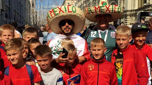 Học sinh Nga chụp ảnh kỷ niệm cùng các cổ động viên Mexico tại Quảng trường Đỏ, Moskva. Ảnh: Latimes.
