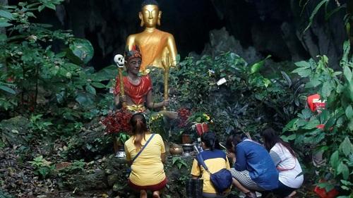 Người thân của đội bóng nhí cầu nguyện trước bức tượng Phật gần hang Tham Luang, Mae Sai, Chang Rai. Ảnh:AP.