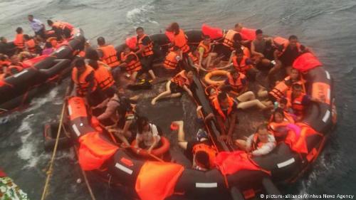 Những hành khách ngồi trên bè phao cứu sinh sau khi tàu chìm. Ảnh:Xinhua.