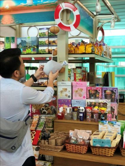 Hành khách xem quà tặng và hàng lưu niệm bày bán tại quầy.