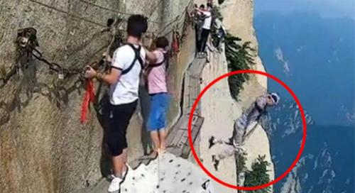 Người đàn ông (trong dấu khoanh tròn đỏ) lao xuống vực khi đang leo núi. Ảnh: Shanghaiist.
