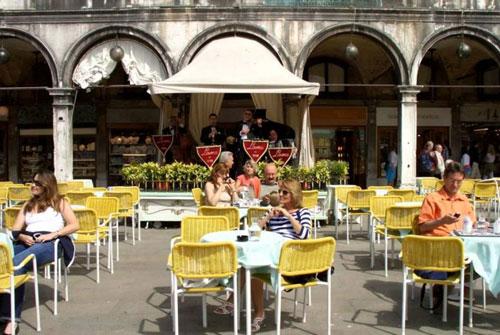 Quán cà phêLavena là địa điểm thu hút đông đúc khách du lịch ghé thăm, do vị trí đẹp, có thể vừa nhâm nhi đồ uống vừa ngắm cảnh toàn bộ quảng trường St Mark nổi tiếng. Ảnh: Youtube.