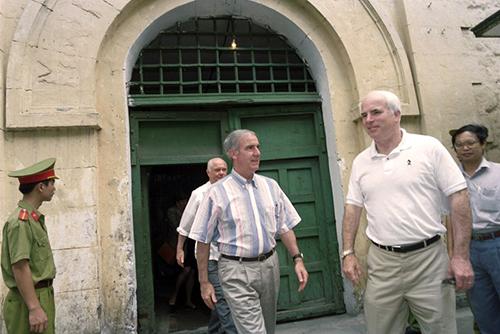 Ông John McCain (ngoài cùng bên phải) cùng dân biểu Pete Peterson (trái) và cựu thượng nghị sĩ John Glenn rời nhà tù Hỏa Lò trong chuyến thăm vào tháng 1/1990. Ảnh: AFP