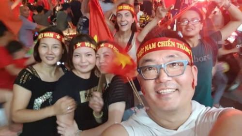 Tak Woo Young (phải) đeo băng-rôn mừng chiến thắng của đội tuyển Việt Nam cùng người dân. Ảnh:NVCC.