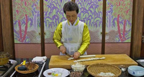 Tiến sĩ về ẩm thực Sook-ja Yoon trong chiếc váy lụa truyền thống đang chuẩn bị những nguyên liệu cho món tteokguk. Đó là những sợi bột gạo trắng gọi là tteok, một đĩa thịt bò thái mỏng và các bát nhỏ đựng gia vị, và một nồi nước dùng đang sôi. Ảnh: BBC.