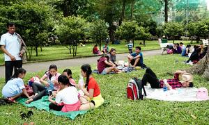 Du khách trải áo mưa, ngủ la liệt trong công viên Sài Gòn