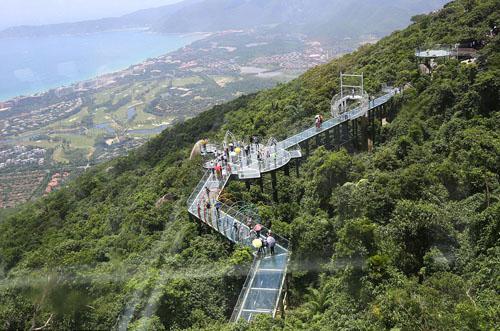 Du khách đang đi bộ trên cây cầu đáy kính đầu tiên tại Hải Nam. Ảnh: REX.
