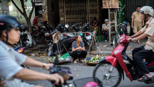 Một phụ nữ bán rong trong phố cổ Hà Nội. Ảnh:JustinMeneguzzi.