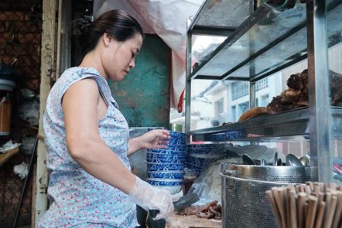 Chị Kim Anh bên góc bếp nhỏ của mình. Ảnh: Di Vỹ.