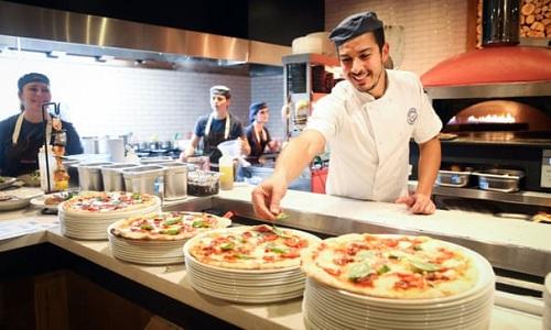 Đầu bếp Messaadia Imad chuẩn bị pizza cho thực khách vào ngày mở cửa trở lại. Toàn bộ nhân viên của Zizi vẫn được trả lương trong thời gian nhà hàng đóng cửa, một số được chuyển tới cơ sở kinh doanh khác. Ảnh: Matt Alexander/PA.
