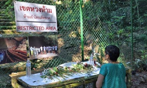 Khách du lịch cầu nguyện ngoài hang Tham Luang. Ảnh:Guardian.
