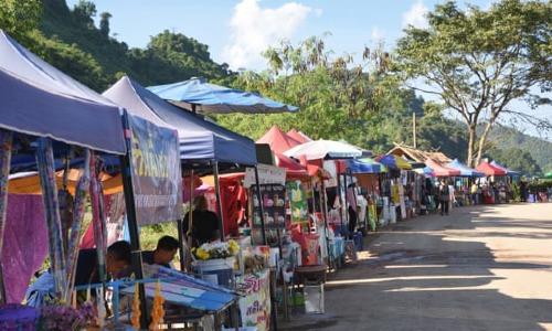 Các quầy hàng lưu niệm và quán ăn mở ra dọc theo con đường đến khu phức hợp hang Tham Luang. Ảnh:Guardian.