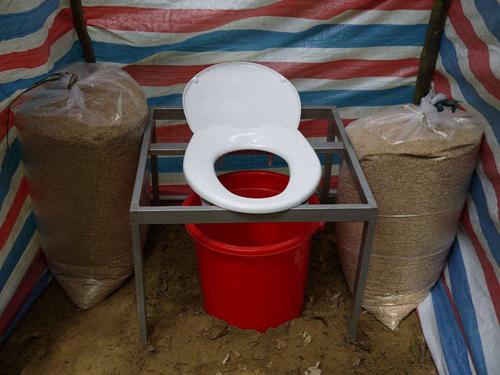 Compost toilet (nhà vệ sinh ủ phân vi sinh) gồm thùng, xô nhựa kín và vỏ trấu, mỗi khi dùng xong sẽ lấy trấu lấp hết chất thải, cứ thế đến khi đầy xô. Trấu có tác dụng khử mùi, hút hết nước và phân hủy chất thải nhanh chóng. Phần chất thải khô này sau 1 - 2 tháng sẽ trở thành phân bón có ích cho cây trồng. Mỗi điểm cắm trại luôn có ít nhất hai khu vệ sinh cho những người đi Sơn Đoòng sử dụng.
