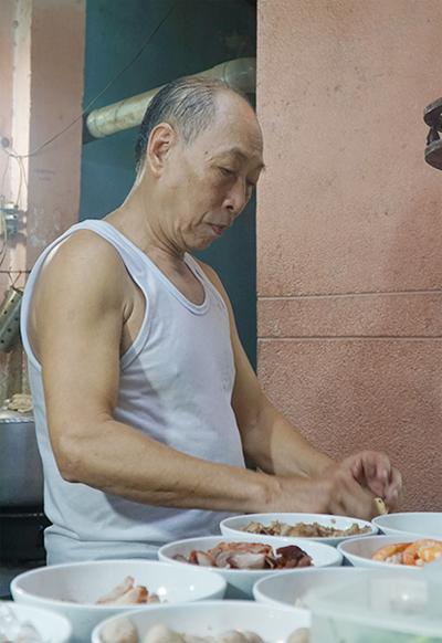 Ông Minh Hoà bên góc bếp thân quen được đặt ở ngay trước quán. Ảnh: Di Vỹ.