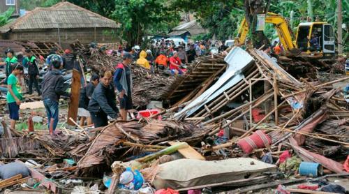 Người dân kiểm tra một ngôi nhà bị hư hại do sóng thần ở Carita, Indonesia. Ảnh: AP.