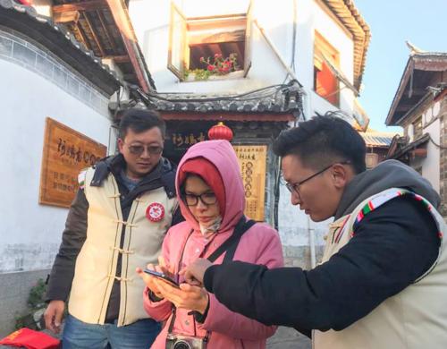 Tình nguyện viên du lịch giúp khách tìm đường tại Lệ Giang cổ trấn.