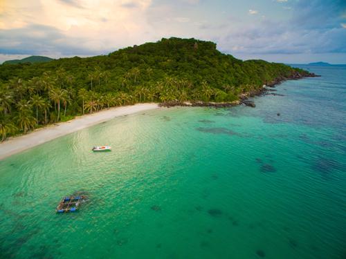 Những bãi cát trắng trải dà, nước biển xanh trongĐược UNESCO công nhận là khu bảo tồn sinh quyển thế giới năm 2006, Phú Quốc là một trong những hòn đảo đẹp nhất trong vịnh Thái Lan. Gần đây, điểm đến này thu hút nhiều sự quan tâm của du khách bởi vẻ đẹp hoang sơ của những bãi biển cát trắng mịn trải dài thoai thoải, nước xanh trong vắt có thể nhìn thấy cả san hô và từng đàn cá tung tăng bơi lượn.Thiên nhiên tại đây hài hòa và yên bình như trong những bức tranh. Những tảng đá lớn phủ rêu xếp chồng lên nhau cùng hàng cây cổ thụ, cây đa trăm tuổi với gốc cây vững chãi trồi lên trên mặt nước, tán cây xòe đủ rộng để che mát cả một vùng biển vắng.