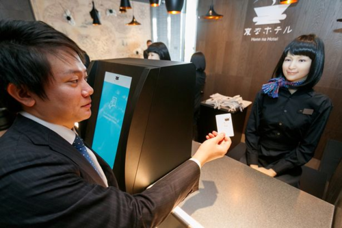 Nhân viên là con người cũng phải giúp robot photo hộ chiếu của các vị khách tại khách sạn Henn-na ở Tokyo. Ảnh: Mirror.