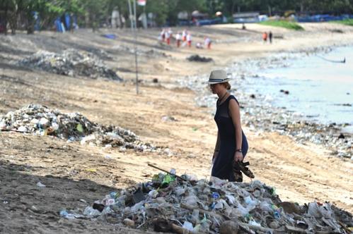 Khách du lịch đi giữa nhữngđống rác được thu gomtrên bãi biển Kuta gần Denpasar, Bali. Ảnh:AFP.